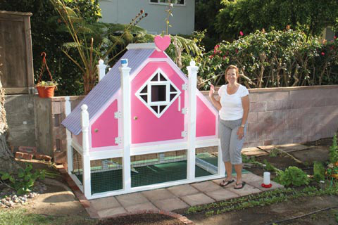 """Paulina Shahin stands in front of the """"Barbie Dream House"""" coop that her husband, Samir, designed and built for their flock of chickens. Most of the finishing touches are completed, including the wire mesh for the run under the house."""