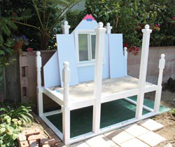 The rear of the coop has also been painted, and the back window installed. All the pre-painted components are now being put together. The side panels are leaning on back wall, painted blue on the inside, pink outside. The coop is placed on a wooden platform made from old gates.