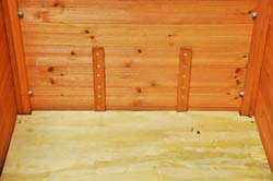 Braces from the original floor were glued and screwed on the inside to reinforce the wall before nest holes were cut.